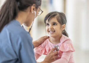 A toddler girl sits on a table during a medical examination. A female medical professional is using a stethoscope to listen to her heartbeat. The child is smiling up at her doctor.